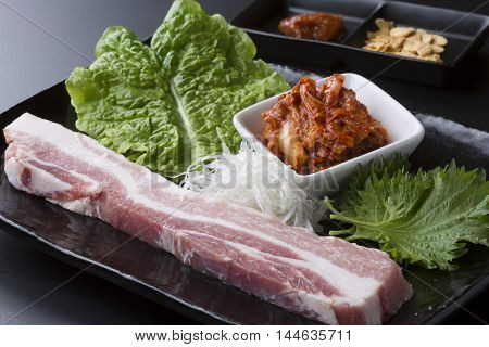 Fresh loin pork with lettuce and kimchi on black dish