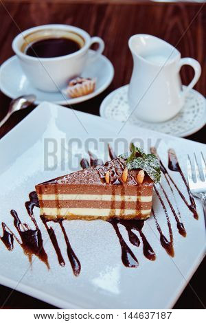 Cheesecake Slice With Melted Chocolate On White Plate And Coffee