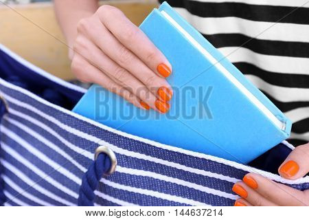 Woman putting book into handbag