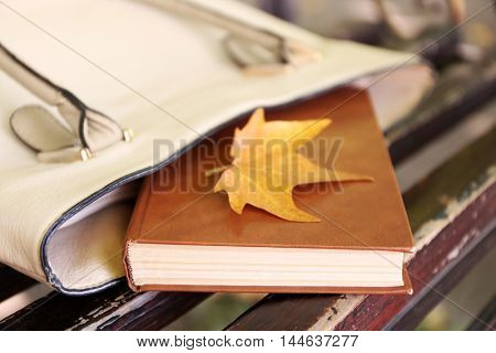 Handbag with book on wooden bench