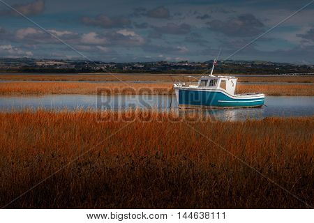 Loughor estuary boat Calm weather over the Loughor Estuary, Penclawdd, North Gower, Swansea.