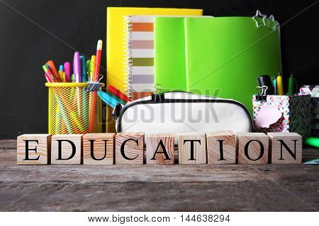 Word EDUCATION and stationery set on table