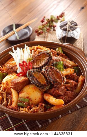 Big bowl of kimchi lunch with abalone mushrooom potatoes beef and noodle on wooden korean table