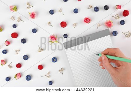 Woman writing in notebook on pattern background with berries and flowers