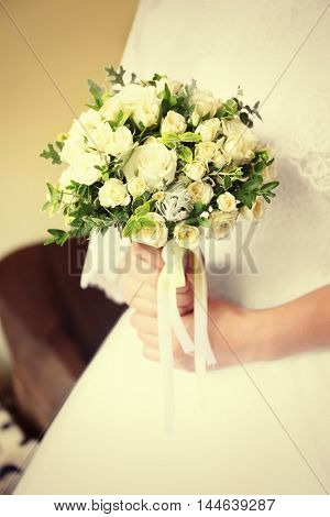 Young fiancee holding flowers, closeup