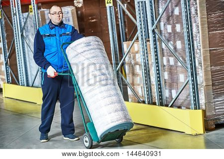 Worker with delivery cart in warehouse