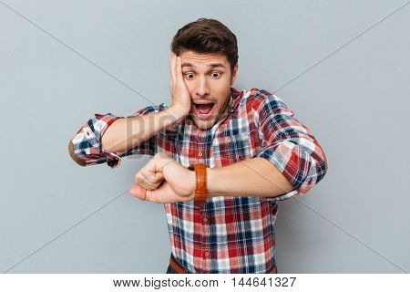 Astonished young man in checkered shirt looking at wristwatch over grey background