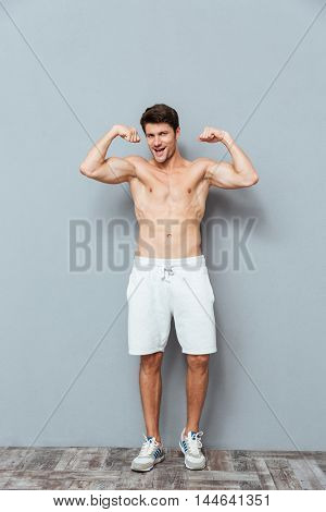 Full length of cheerful attrative young man athlete standing and showing biceps over grey background