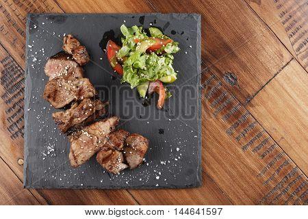 Pork steak pieces with salad. Wooden background.