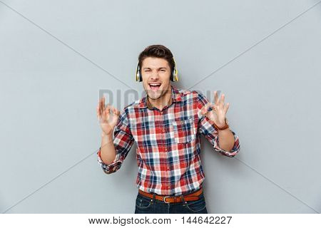 Cheerful young man in headphones showing ok sign and listening to music over grey background