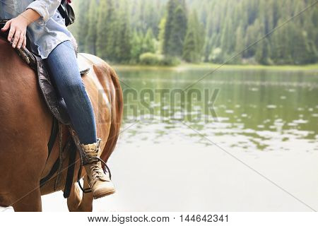Girl riding horse near lake