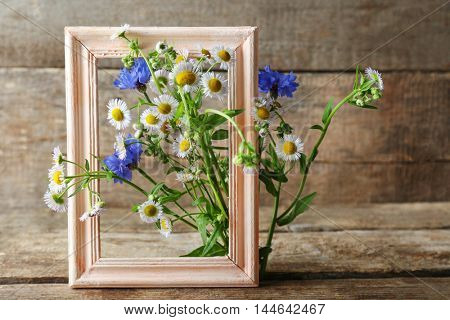 Retro frame with chamomile and bluettes on wooden background