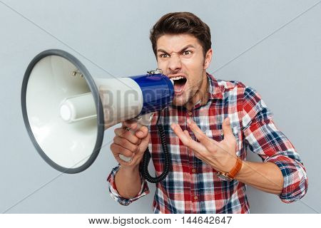 Portrait of a man screaming in megaphone isolated on a gray background