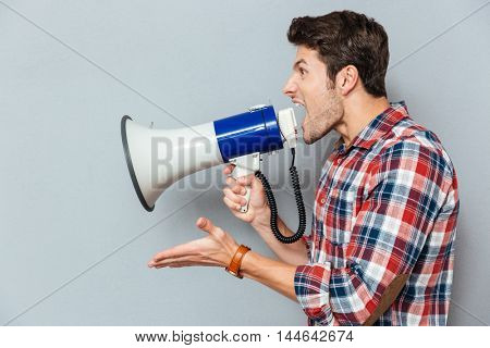 Side view portrait of a casual man yelling into megaphone isolated on a gray background