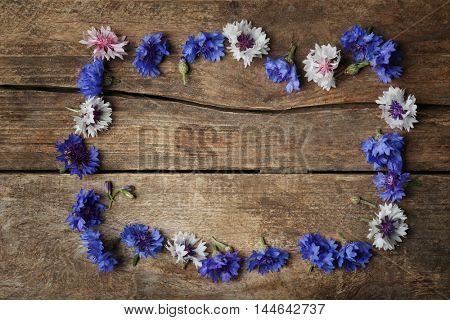 Frame made of bluett flowers on wooden background