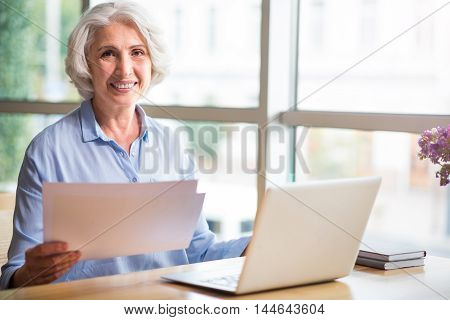 Life is good. Cheerful content senior woman holding papers and smiling while sitting at the table