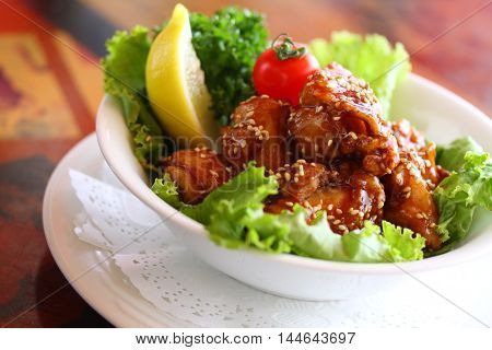 Fried chicken with lettuce and lemon on white bowl in restaurant