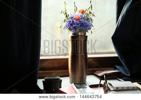 Lovely wild flowers in thermos on a railway coach table