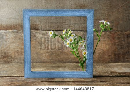 Retro frame with chamomile flowers on wooden background