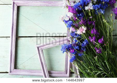 Retro frames with wild flowers on wooden background, top view