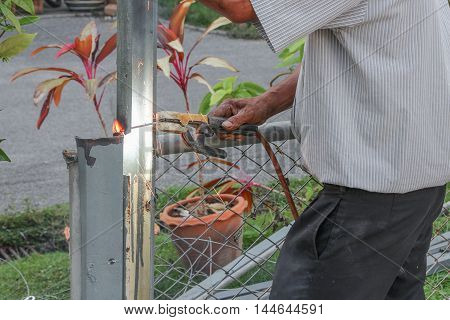 Welder working a metal. Not wearing the glove causing a danger: Select focus  with shallow depth of field :