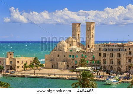 View of  Molfetta old town: the harbor and the Old Cathedral (Duomo Vecchio).ITALY(Apulia).Old Cathedral of Molfetta in Romanesque style:church with three domes aligned with side half-barrels.