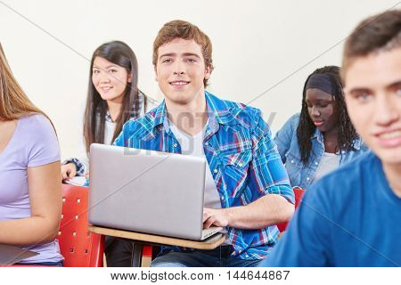 Student in class with a laptop with a smile