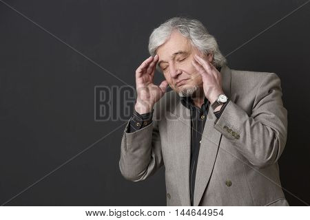 Portrait of professor man of university or colleage posing with his eyes closed in studio. Teacher in business suit touching his face isolated on black background.