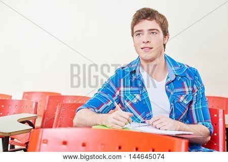 Motivated student taking notes in class in high school