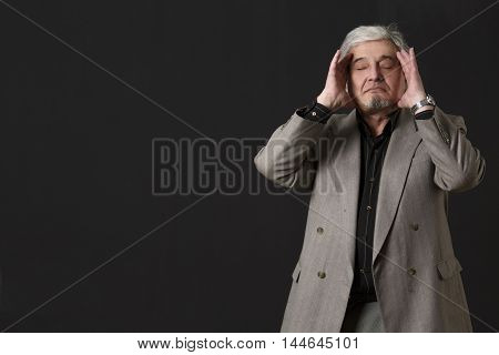 Portrait of professor man in business suit touching his face and posing with closed eyes isolated on black. Teacher of university or colleage in studio.