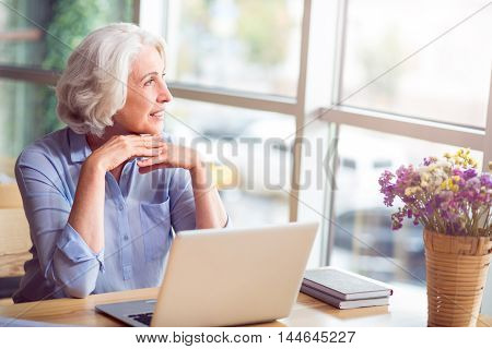 Enjoy every moment. Delighted smiling senior woman sitting at the table and looking in the window while resting in the cafe