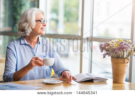 Enjoy every day. Cheerful content smiling woman drinking coffee and looking in the window while resting at the table in the cafe