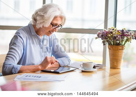 Modernize your outlook. Positive delighted senior woman smiling and using tablet while sitting at the table
