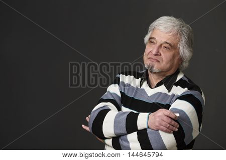 Portrait of handsome professor man of university or colleage posing with his arms crossed or folded isolated on black background in studio.