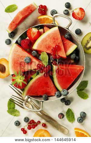 Watermelon, blueberry and mint leaves on white marble background. Summer fruit concept.