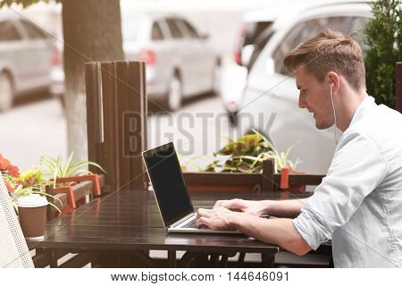 Handsome man with laptop listening music in cafe