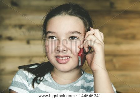 Little teen girl calling by phone