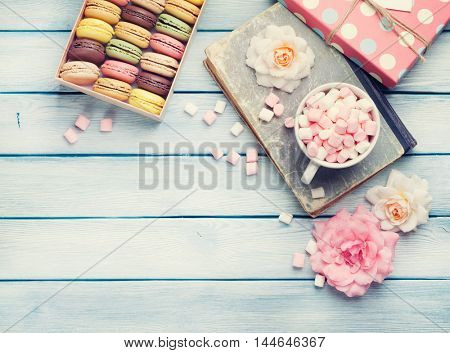Colorful macaroons in a gift box and marshmallow in coffee cup on wooden table. Sweet macarons and flowers. Top view with copy space. Retro toned