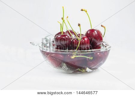 Cherry isolated soak in a glass container on white background , Fresh red cherries sweet palatable