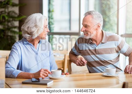Pleasant time spending. Cheerful delighted couple sitting at the table and talking while drinking coffee