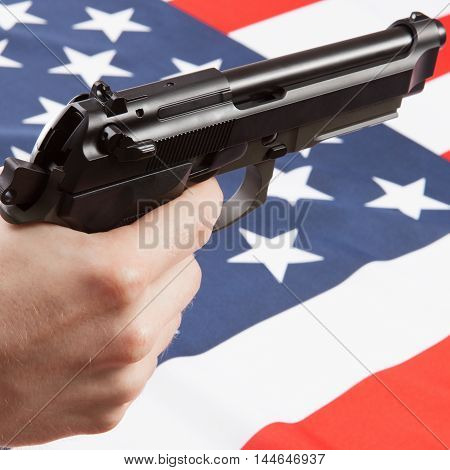 Gun In Hand With Ruffled National Flag On Background - United States