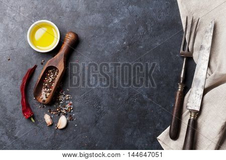 Herbs and spices. Cooking ingredients and utensils. Chili, olive oil, salt and pepper. Top view over stone table with copy space for your recipe
