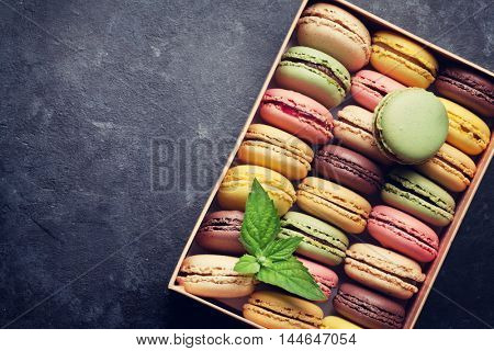 Colorful macaroons in a gift box on stone table. Sweet macarons. Top view with copy space. Retro toned