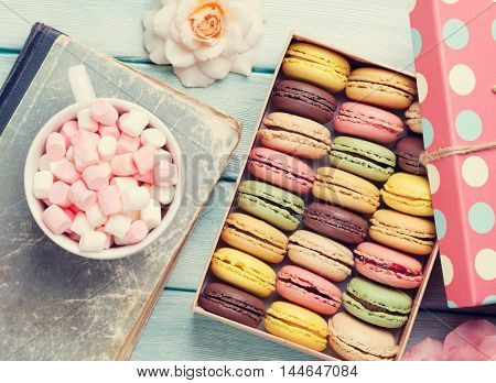 Colorful macaroons in a gift box and marshmallow in coffee cup on wooden table. Sweet macarons and flowers. Top view. Retro toned