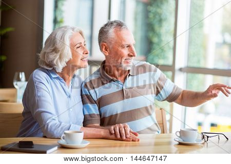 Have a look. Delighted senior loving couple sitting in the cafe and looking in the window while resting