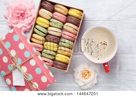 Colorful macaroons in a gift box and coffee cup on wooden table. Sweet macarons and flowers. Top view