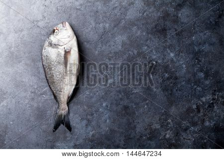 Raw dorado fish. Top view with copy space on stone table