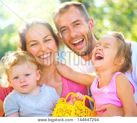 Happy joyful young family with children. Father, mother and little kids having fun outdoors in orchard garden, playing together in summer park. Mom, Dad, kids laughing and hugging, enjoying nature