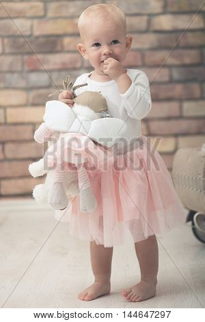 Cute baby girl playing with plush toy