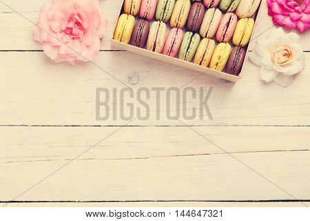 Colorful macaroons in a gift box on wooden table. Sweet macarons and flowers. Top view with copy space. Retro toned